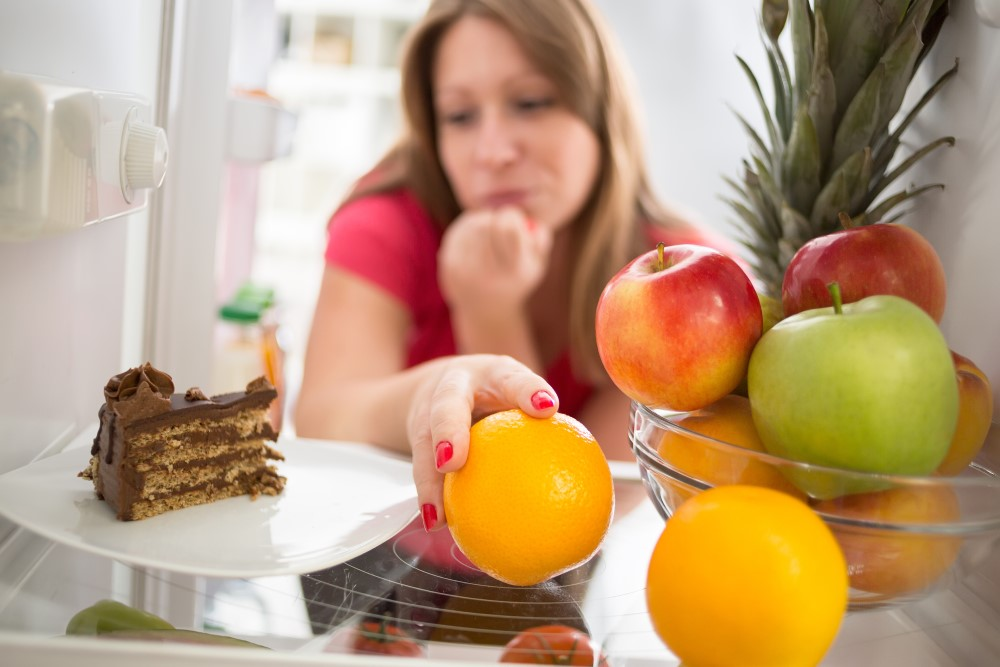 A women struggles with the willpower to eat fruit instead of cake.