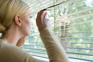 Woman looking out of a window through the blinds.